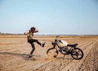 man kicking dirt at bike